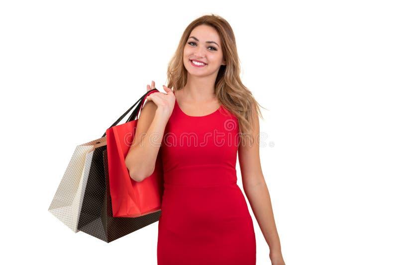Ritratto di giovane donna sorridente felice con i sacchetti della spesa, isolato sopra fondo bianco fotografie stock