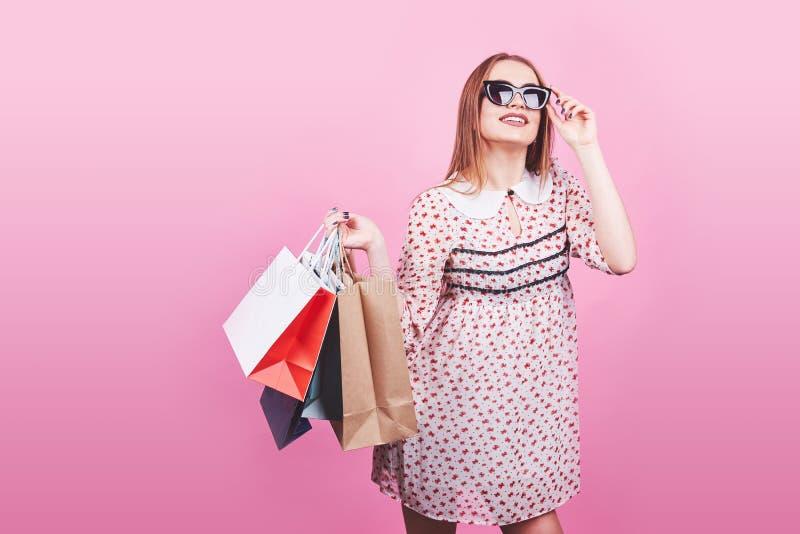 Ritratto di giovane donna sorridente felice con i sacchetti della spesa sui precedenti rosa fotografia stock