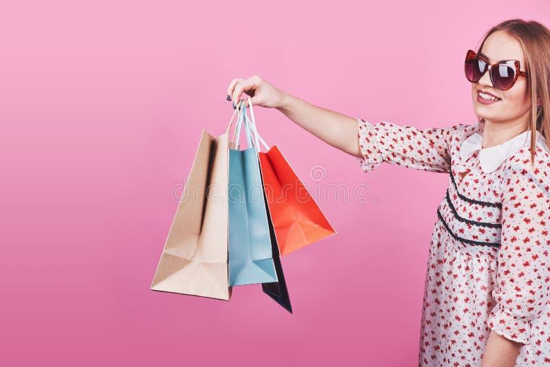 Ritratto di giovane donna sorridente felice con i sacchetti della spesa sui precedenti rosa fotografia stock libera da diritti
