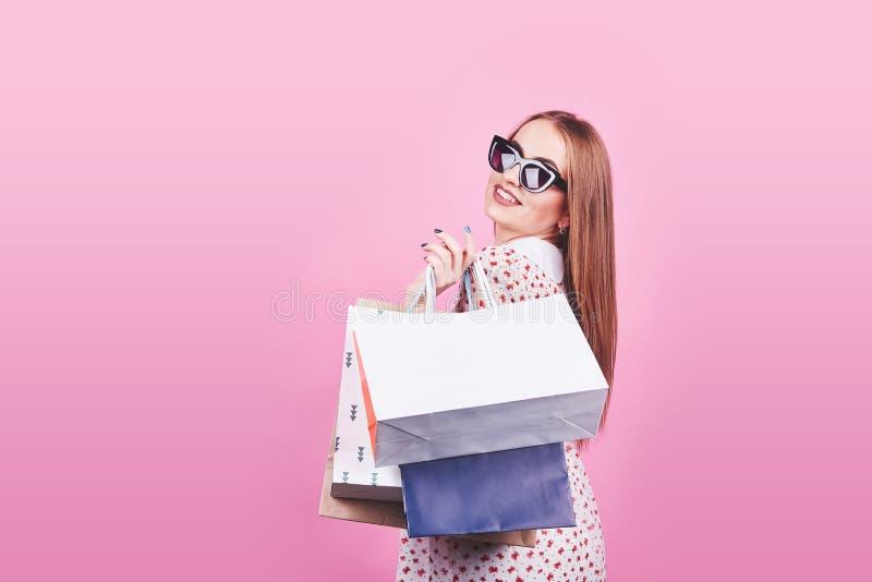 Ritratto di giovane donna sorridente felice con i sacchetti della spesa sui precedenti rosa fotografie stock libere da diritti