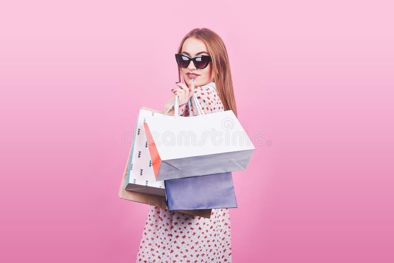 Ritratto di giovane donna sorridente felice con i sacchetti della spesa sui precedenti rosa immagini stock libere da diritti