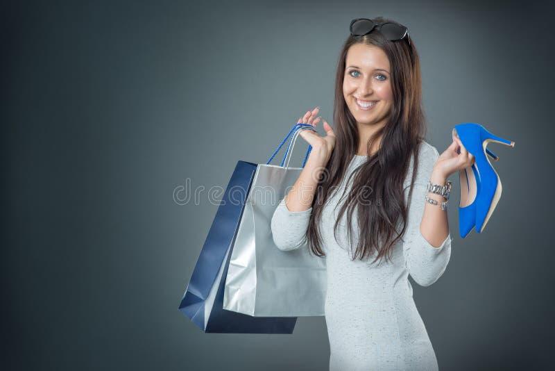 Ritratto di giovane donna sorridente felice con la carta di credito e le scarpe dei sacchetti della spesa immagine stock