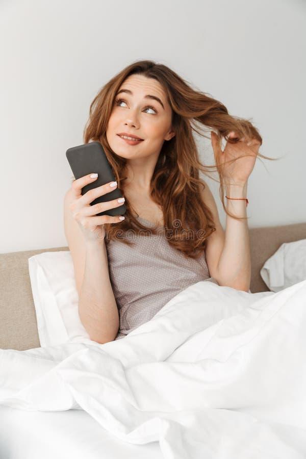 Ritratto di giovane donna sveglia che riposa a letto dopo il sonno con il whi fotografia stock