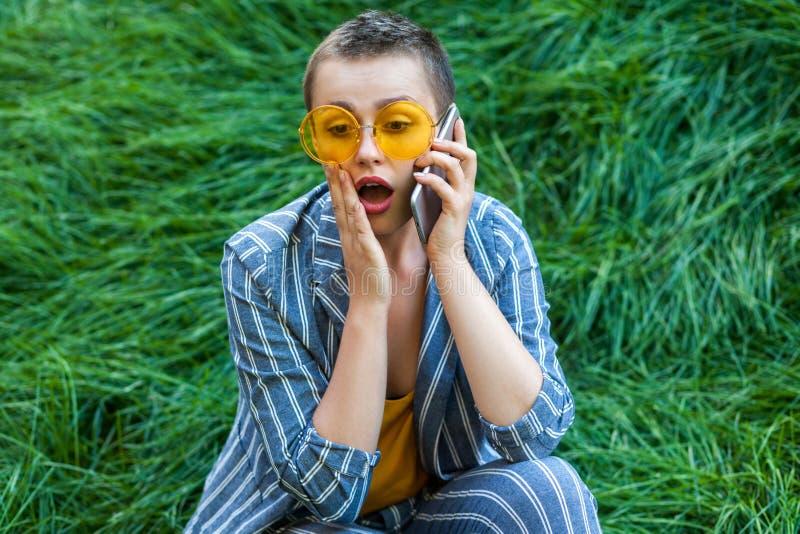 Ritratto di giovane donna sveglia colpita dei capelli di scarsità in vestito a strisce blu casuale, camicia gialla e vetri seden immagine stock libera da diritti