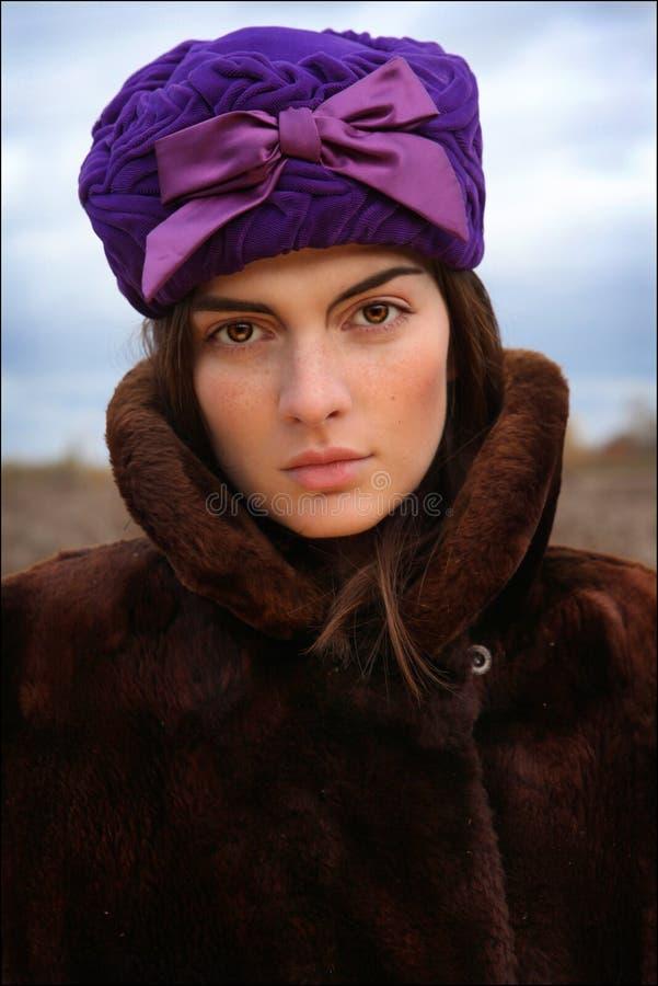 Ritratto di giovane donna in un cappotto ed in un cappello di pelliccia fotografia stock