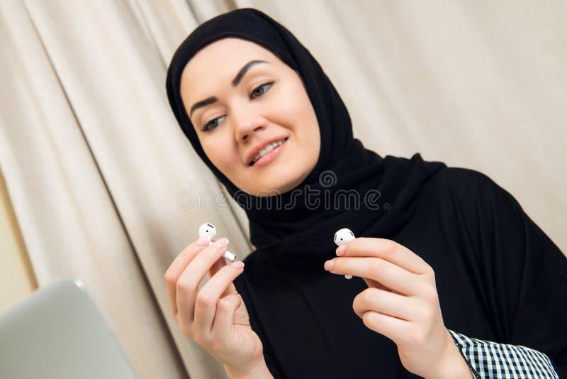 Ritratto di giovane e donna musulmana attraente in un turbante o in un hijab che ascolta il flusso continuo della musica sul suo  immagini stock