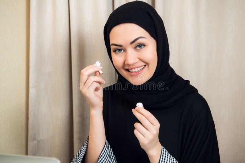 Ritratto di giovane e donna musulmana attraente in un turbante o in un hijab che ascolta il flusso continuo della musica sul suo  immagine stock