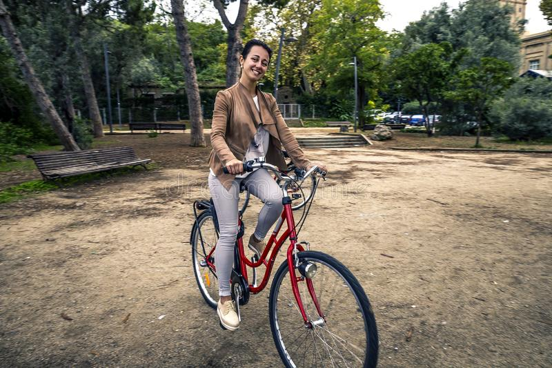 Ritratto di giovane e guida attraente della donna sulla bicicletta rossa immagini stock libere da diritti