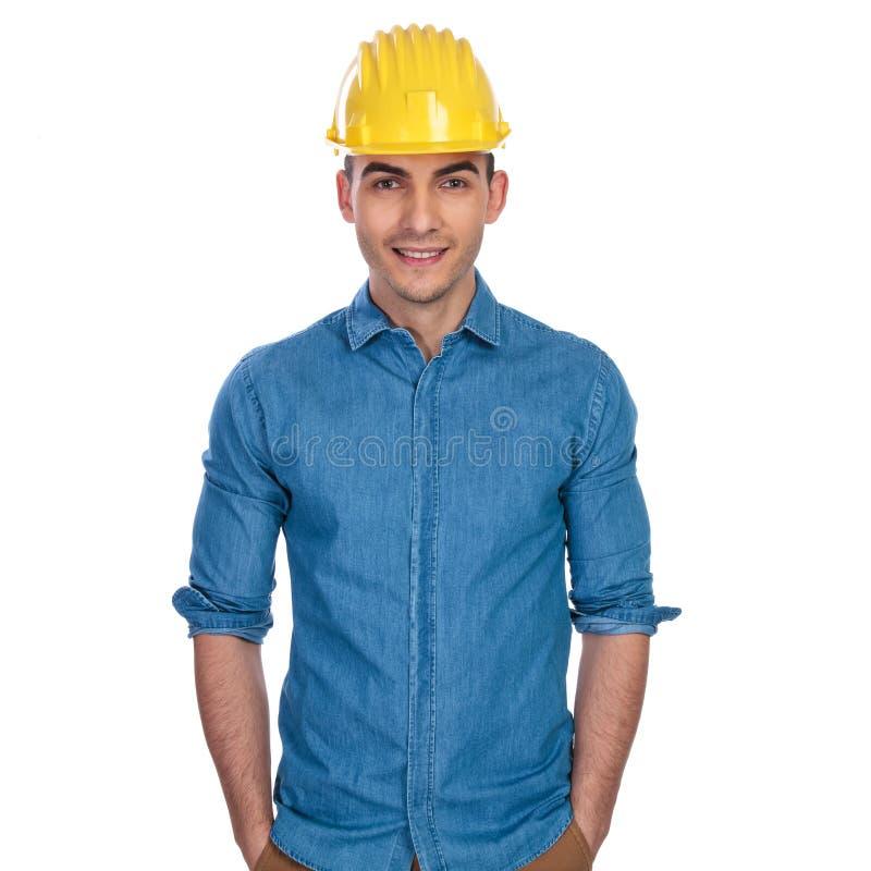 Ritratto di giovane e studente rilassato dell'ingegnere che indossa casco giallo immagine stock