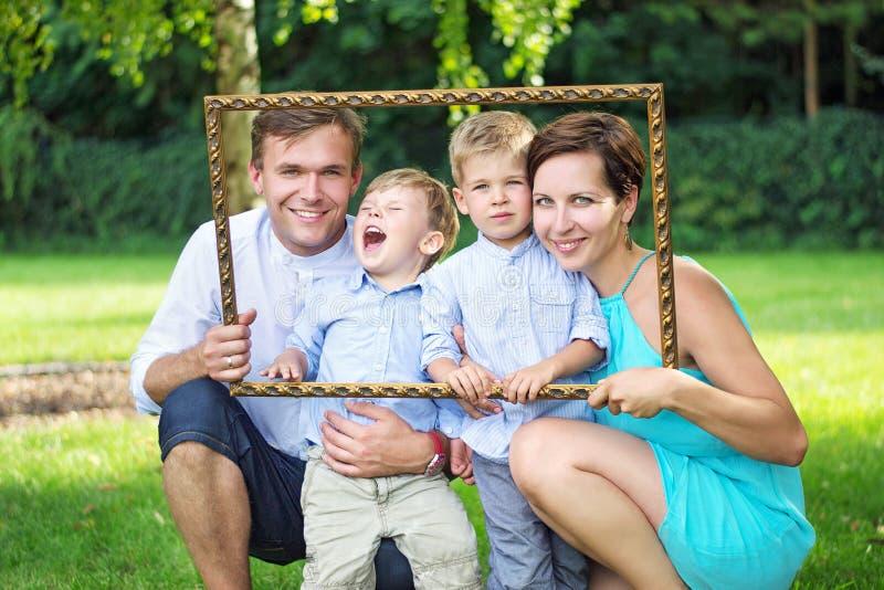 Ritratto di giovane famiglia che posa nel giardino immagine stock libera da diritti