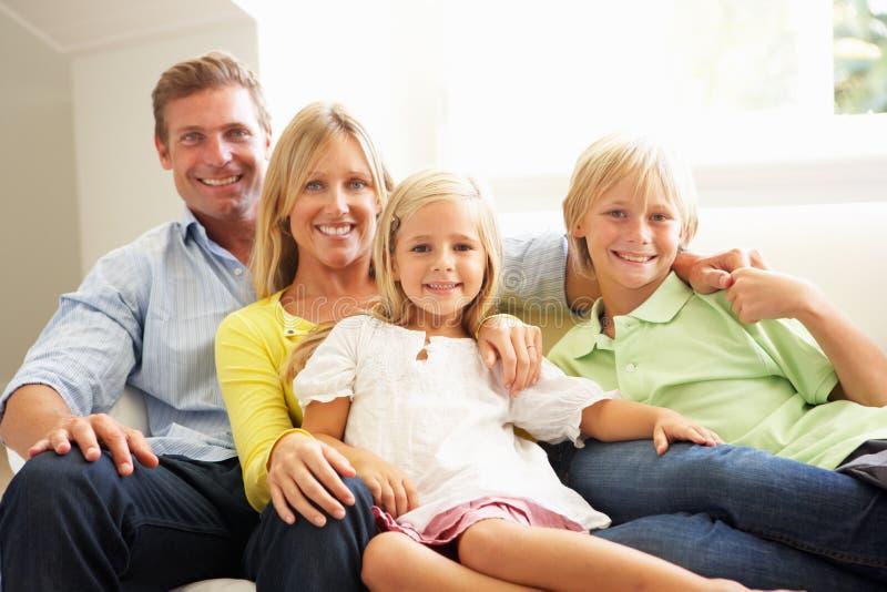 Ritratto di giovane famiglia che si distende insieme sul sofà immagini stock