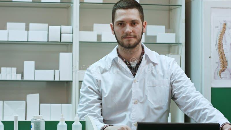 Ritratto di giovane farmacista maschio che esamina macchina fotografica e sorridere immagini stock