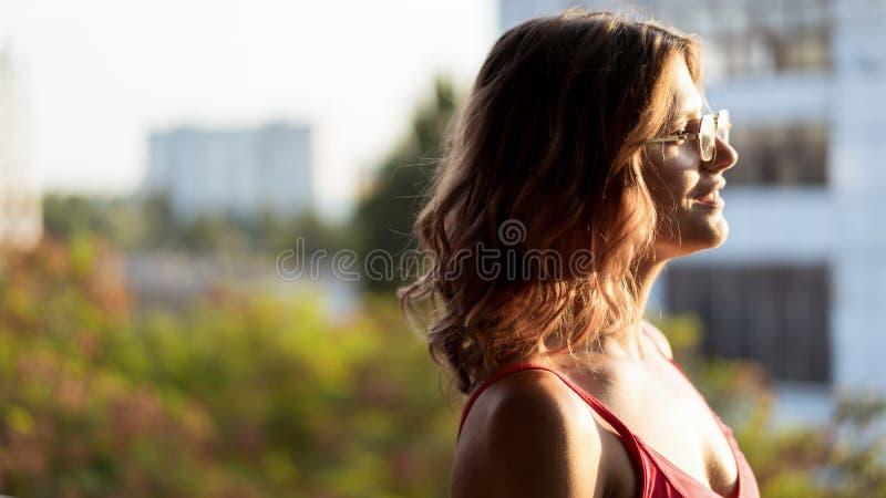 Ritratto di giovane femmina in vetri e con capelli ricci immagini stock