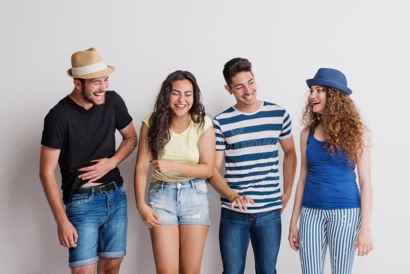 Ritratto di giovane gruppo allegro di amici con i cappelli che stanno in uno studio, ridente fotografia stock libera da diritti