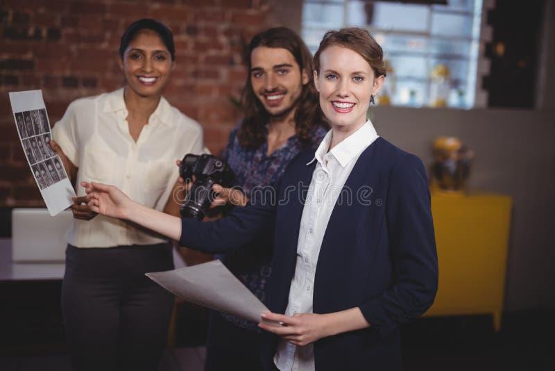 Ritratto di giovane gruppo creativo sorridente che discute collage fotografie stock