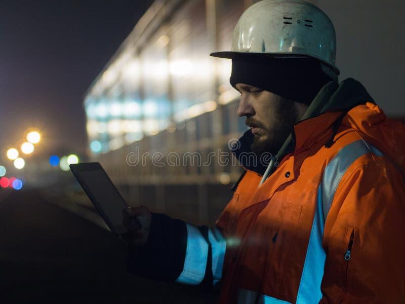 Ritratto di giovane ingegnere che lavora alla compressa durante i otdoors del hignt in casco e rivestimento riflettente fotografia stock libera da diritti