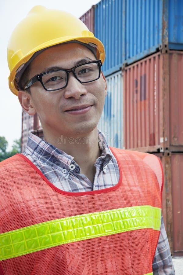 Ritratto di giovane ingegnere sorridente in abiti da lavoro protettivi all'aperto in un'iarda di spedizione fotografia stock