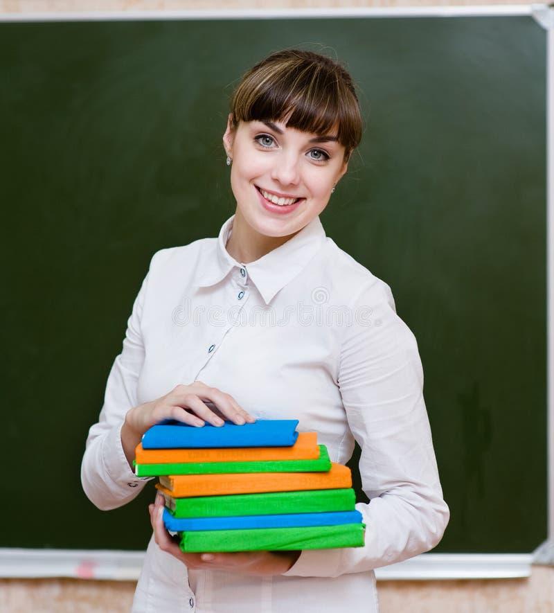 Ritratto di giovane insegnante con i libri fotografia stock