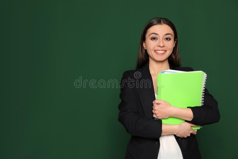 Ritratto di giovane insegnante con i taccuini su fondo verde spazio immagini stock