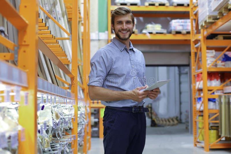 Ritratto di giovane lavoratore sorridente del magazzino che lavora in un deposito della vendita all'ingrosso di cash and carry immagini stock libere da diritti