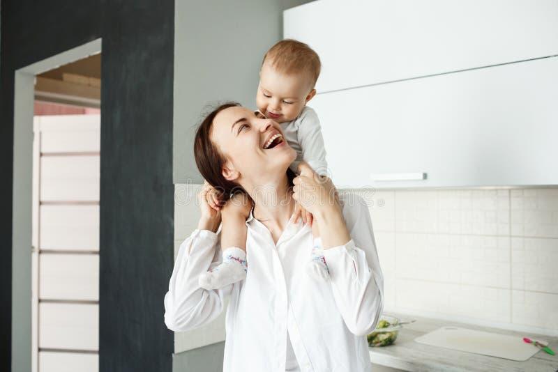 Ritratto di giovane madre felice che tiene il suo piccolo bambino prezioso sulle spalle, esaminante lo e ridente mentre bambino fotografia stock