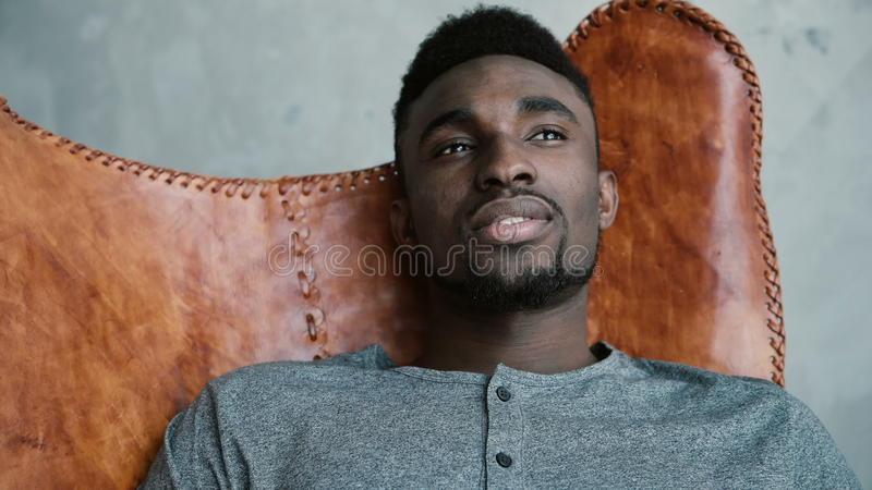 Ritratto di giovane maschio africano che si siede in sedia di cuoio, pensando a qualcosa ed a sorridere L'uomo guarda meditatamen fotografia stock