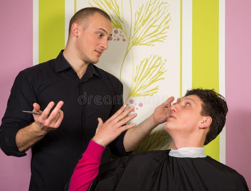 Ritratto di giovane maschio infelice al salone di lavoro di parrucchiere fotografia stock libera da diritti