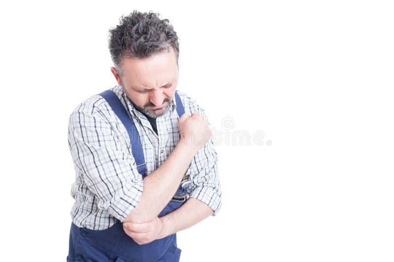 Ritratto di giovane meccanico che ha dolore in braccio danneggiato fotografia stock libera da diritti