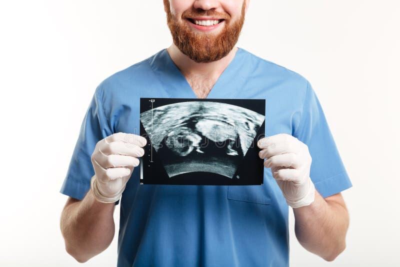 Ritratto di giovane medico maschio sorridente che mostra radiografia fotografia stock
