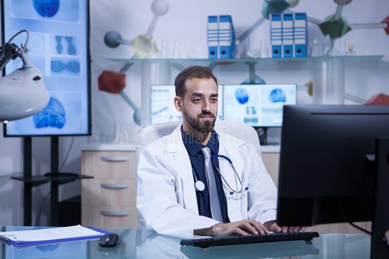 Ritratto di giovane medico nel funzionamento delle camice nel suo ufficio dell'ospedale immagine stock libera da diritti