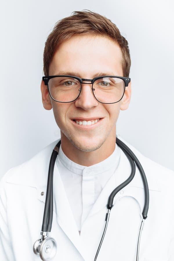 Ritratto di giovane medico su un fondo bianco, interno nello studio, con uno stetoscopio sul collo fotografia stock