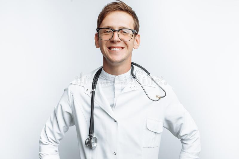 Ritratto di giovane medico su un fondo bianco, interno nello studio, con uno stetoscopio sul collo immagine stock libera da diritti