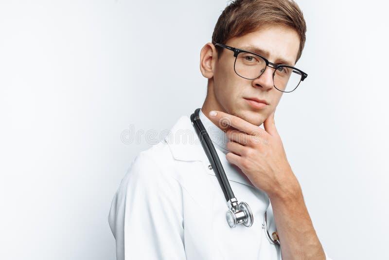 Ritratto di giovane medico su un fondo bianco, interno nello studio, con uno stetoscopio sul collo fotografie stock