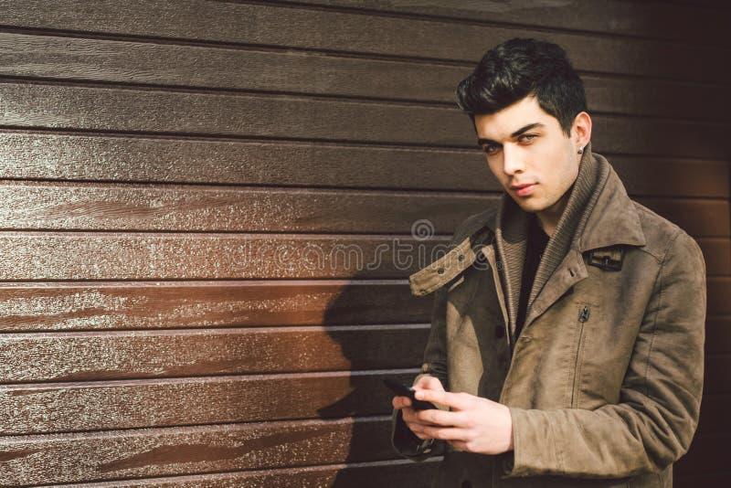 Ritratto di giovane modello maschio turco bello della brunetta Mediterranea della corsa in cappotto di cuoio facendo uso del tele immagine stock