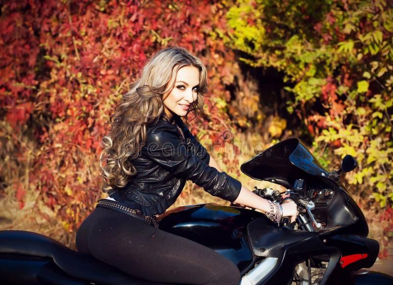 Ritratto di giovane motociclista biondo attraente della donna che posa su lei fotografie stock