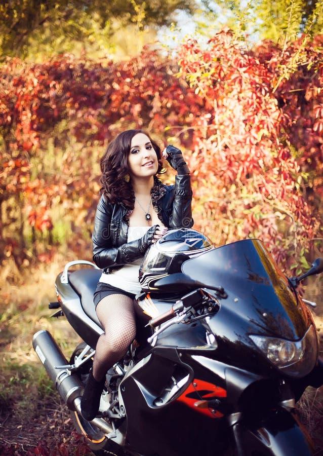 Ritratto di giovane motociclista castana attraente della donna che posa sulla h fotografia stock