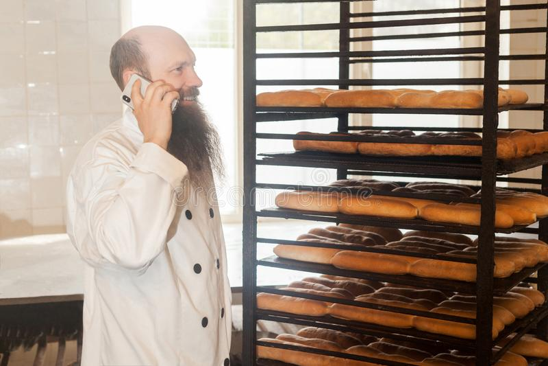 Ritratto di giovane panettiere adulto felice dell'uomo d'affari con la barba lunga nella condizione uniforme bianca nel forno ed  fotografie stock libere da diritti