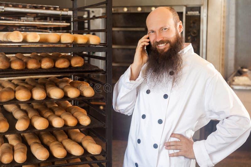 Ritratto di giovane panettiere adulto felice dell'uomo d'affari con la barba lunga nella condizione uniforme bianca nel forno ed  immagine stock