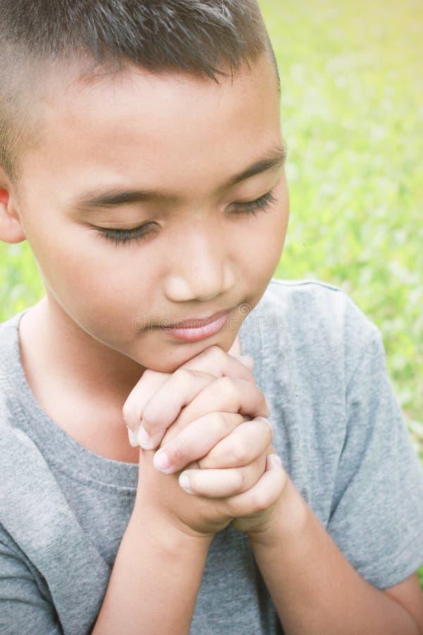 Ritratto di giovane pregare asiatico del ragazzo immagini stock libere da diritti