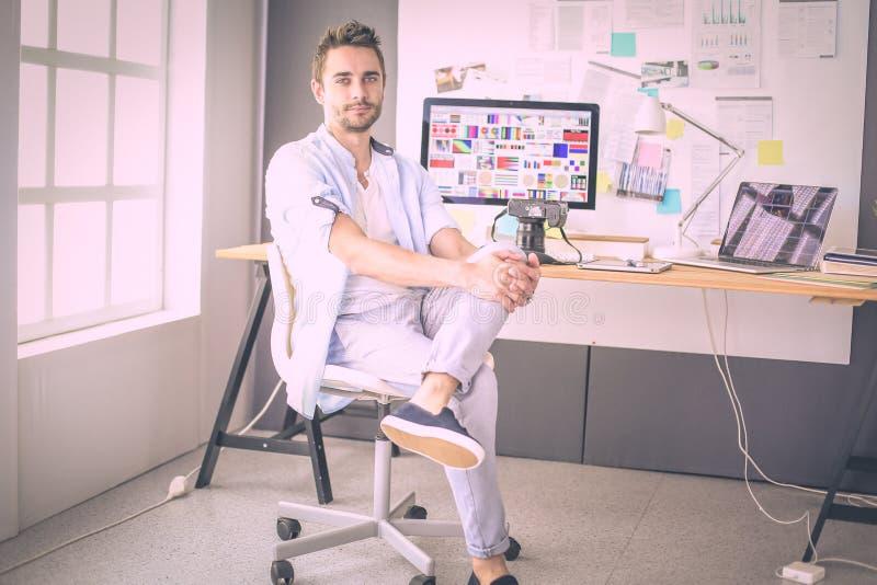 Ritratto di giovane progettista che si siede allo studio grafico davanti al computer portatile ed al computer mentre lavorando on immagine stock libera da diritti