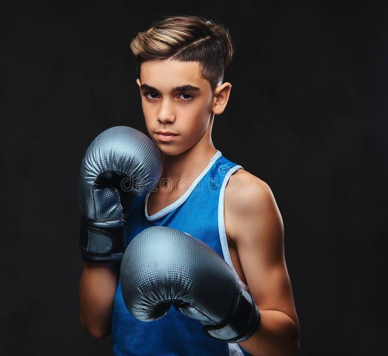 Ritratto di giovane pugile bello nei guanti d'uso degli abiti sportivi Isolato sui precedenti scuri immagini stock libere da diritti