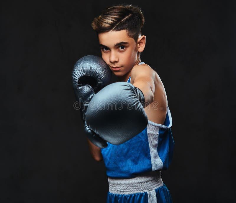 Ritratto di giovane pugile bello nei guanti d'uso degli abiti sportivi Isolato sui precedenti scuri immagine stock