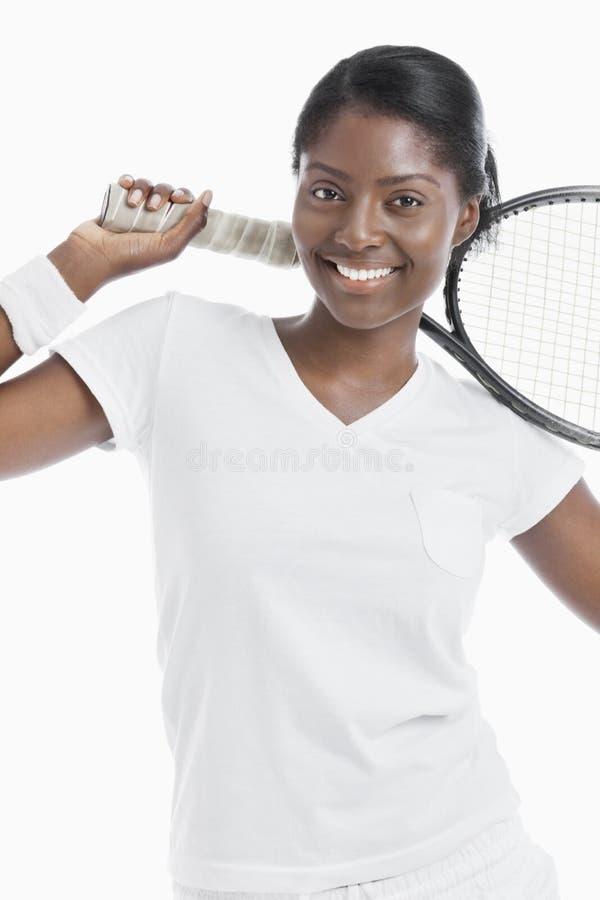 Ritratto di giovane racchetta femminile della tenuta del tennis sopra fondo bianco immagine stock