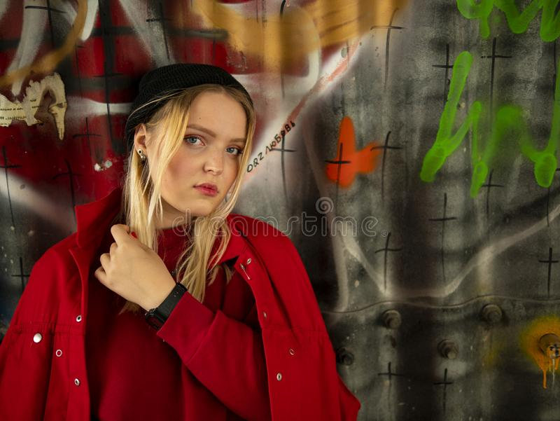 Ritratto di giovane ragazza attraente dei pantaloni a vita bassa in un cappello tricottato contro la parete con le iscrizioni immagine stock libera da diritti