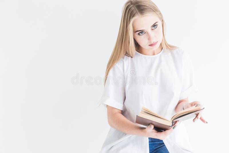Ritratto di giovane ragazza bionda alla moda in maglietta bianca e blue jeans che legge un libro su un fondo bianco immagine stock libera da diritti