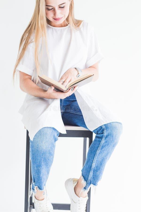 Ritratto di giovane ragazza bionda alla moda in maglietta bianca e blue jeans che legge un libro su un fondo bianco fotografie stock