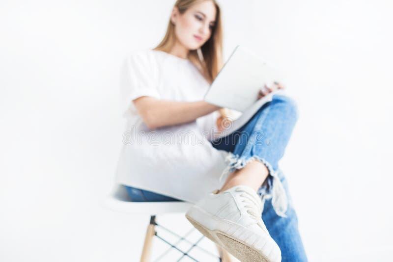 Ritratto di giovane ragazza bionda alla moda in maglietta bianca e blue jeans facendo uso di una compressa su un fondo bianco immagine stock