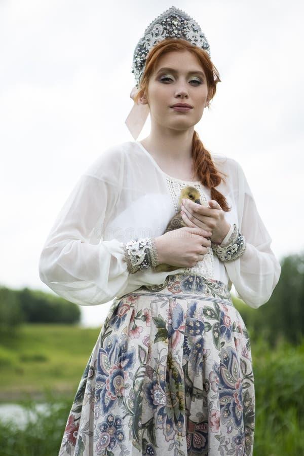 Ritratto di giovane ragazza caucasica delicata che posa tenendo anatroccolo nel vestito russo da stile e nell'aria aperta di Koko immagini stock