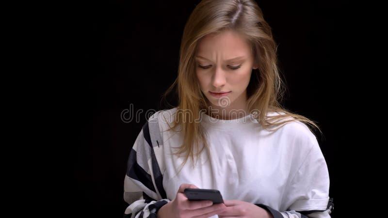 Ritratto di giovane ragazza dai capelli lunghi caucasica in camicia attentamente che funziona con lo smartphone su fondo nero fotografia stock