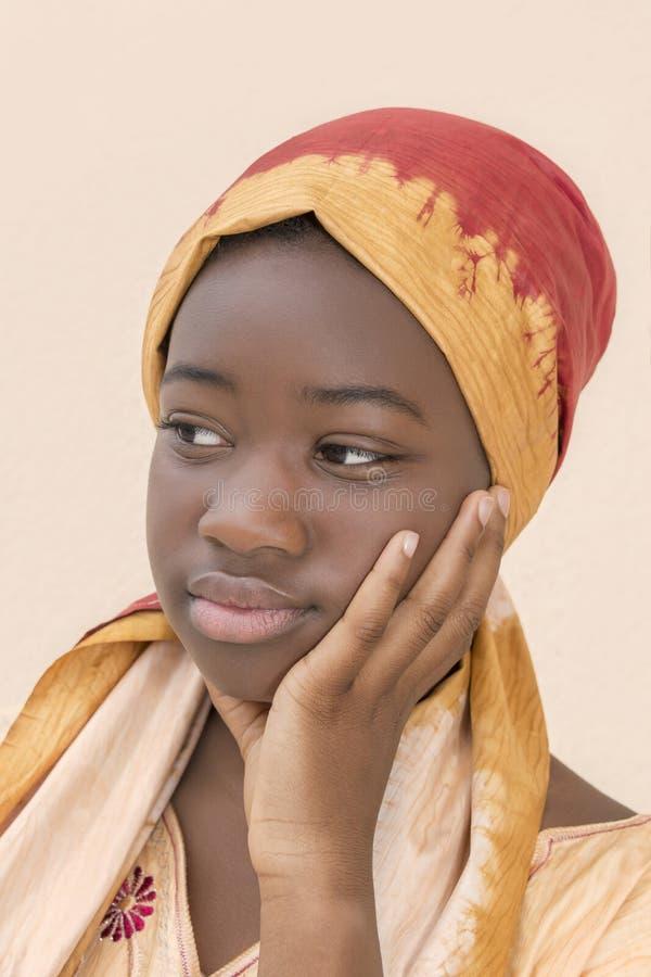 Ritratto di giovane ragazza di afro che indossa un foulard tradizionale fotografia stock